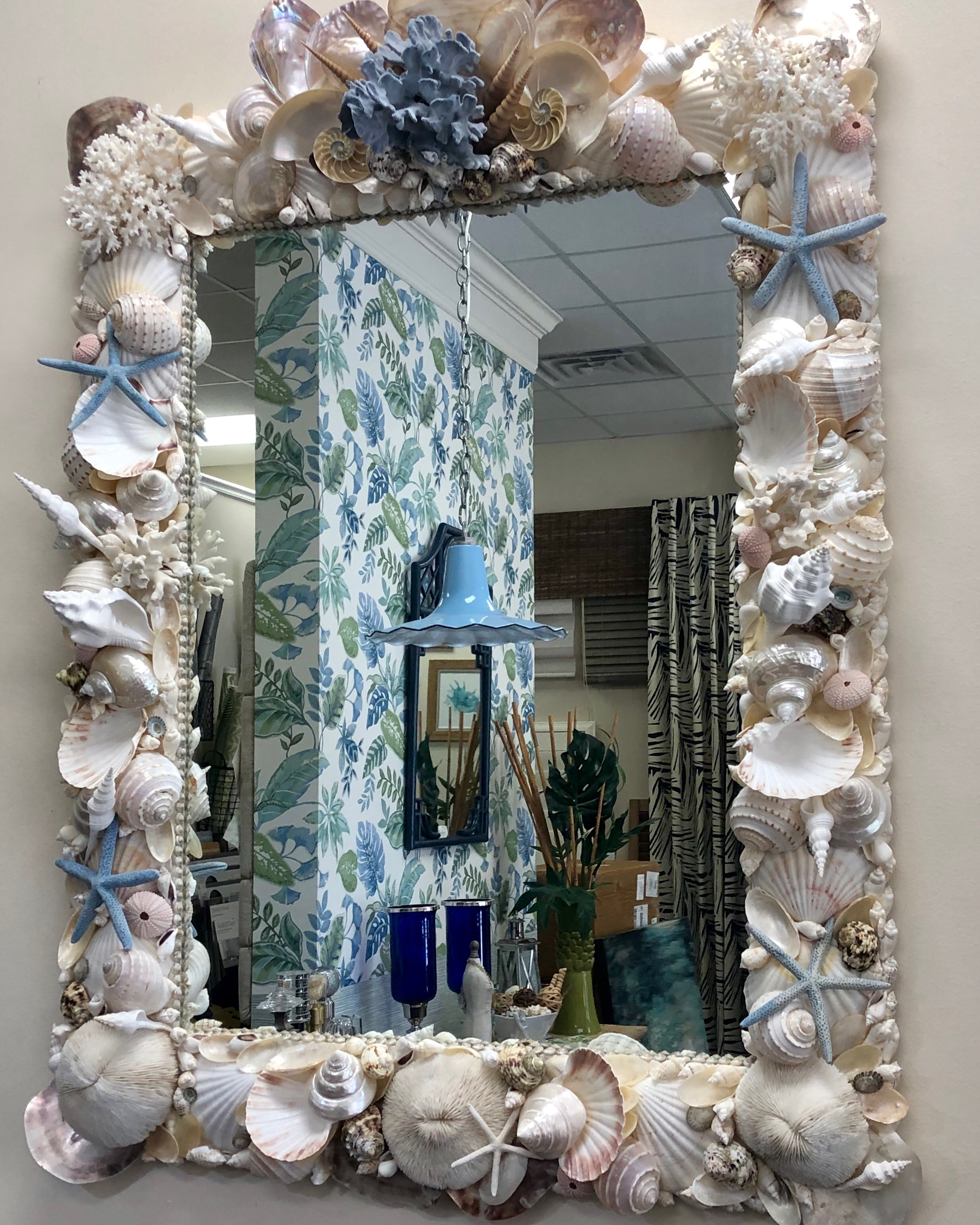 Large square mirror made with large white shells and blue coral. Reflection in the mirror shows blue floral wallpaper and blue lamp