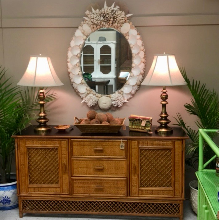 Serving table made from vintage rattan with a pair a lamps with white shades on either side of an oval mirror made with shells
