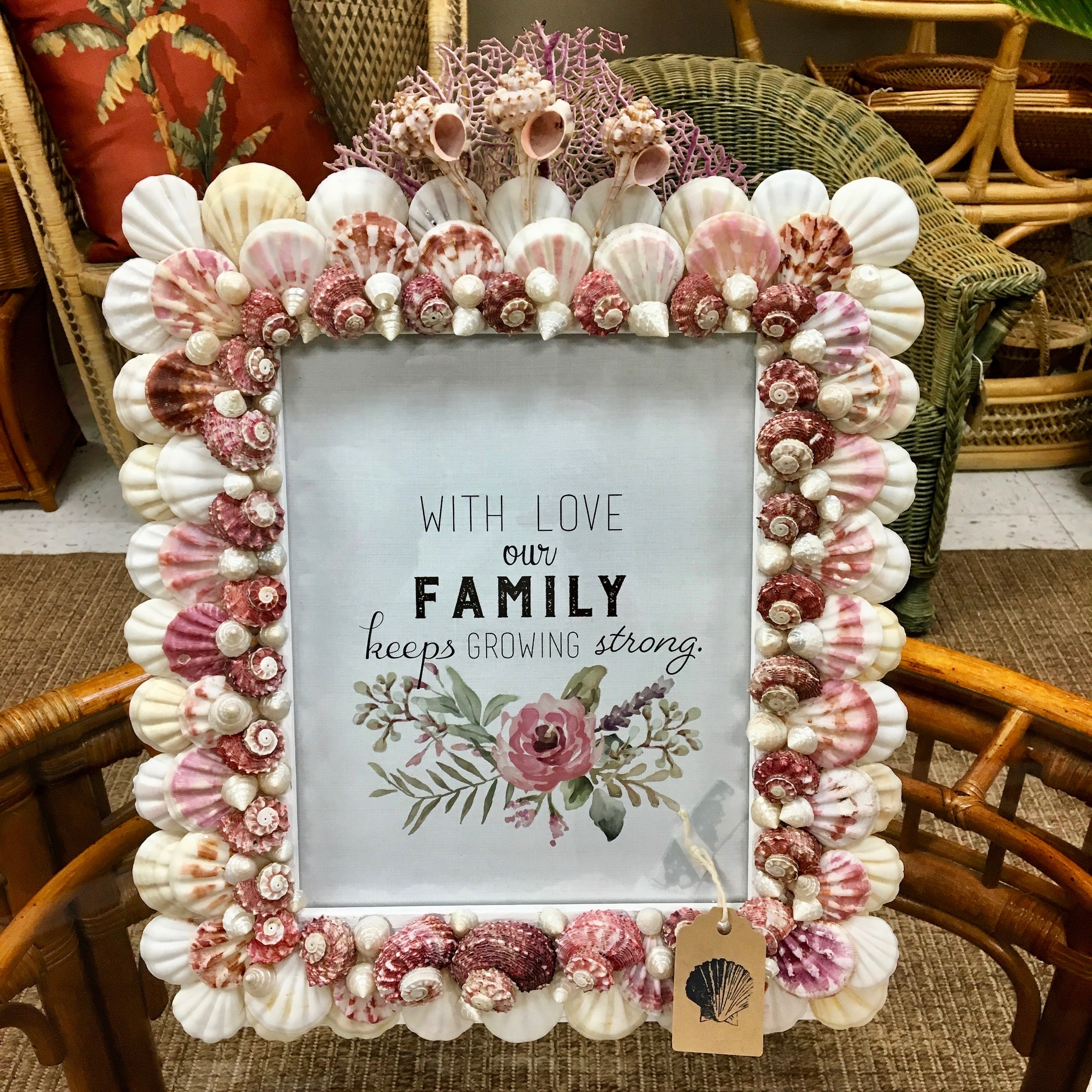 Shell picture frame made with pink and white shells. Inside the frame reds family and has flowers.