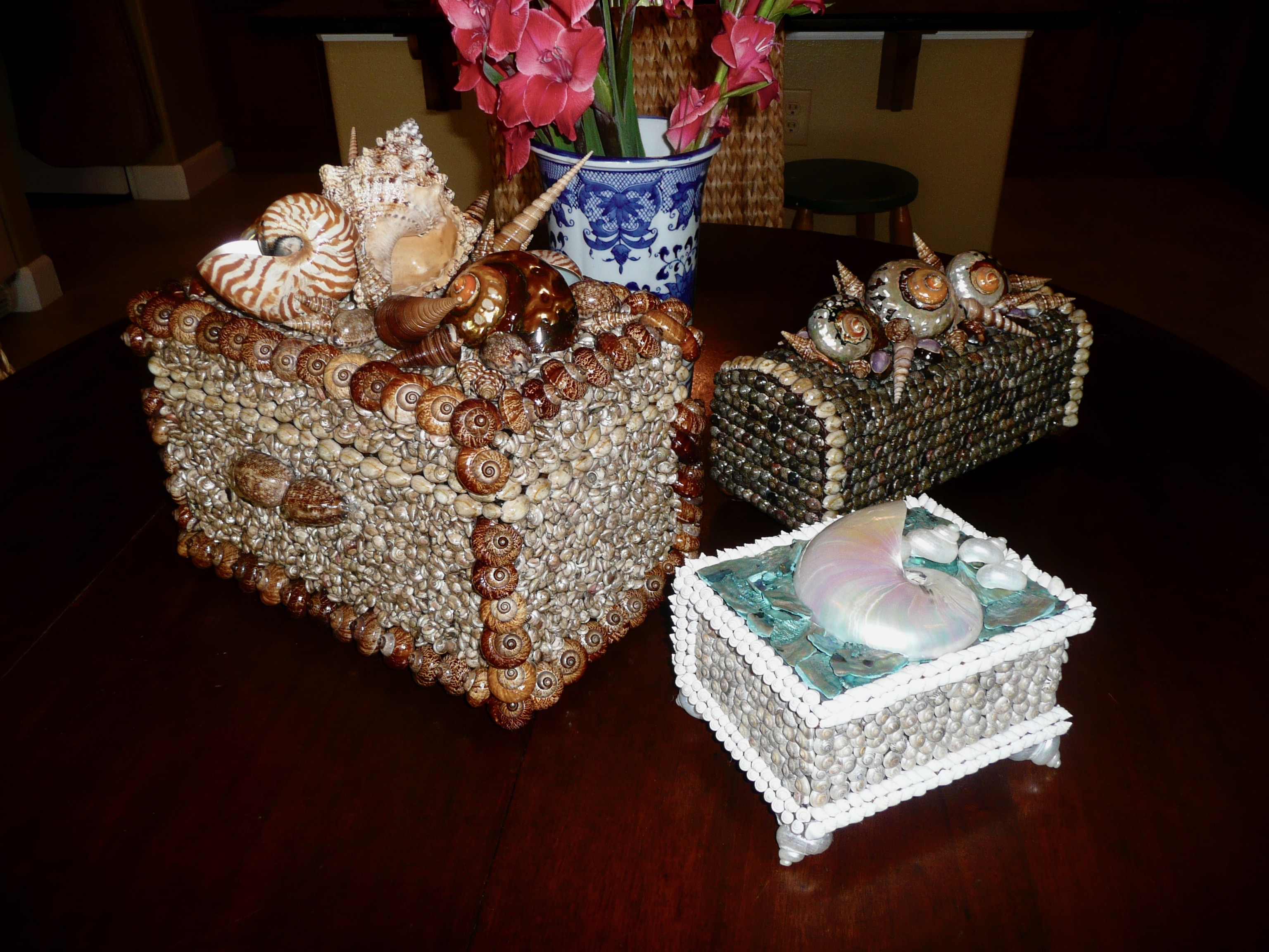 Three small boxes are made with different color sea shells. they sit together on a dark wood table with a blue and white vase of flowers behind them.