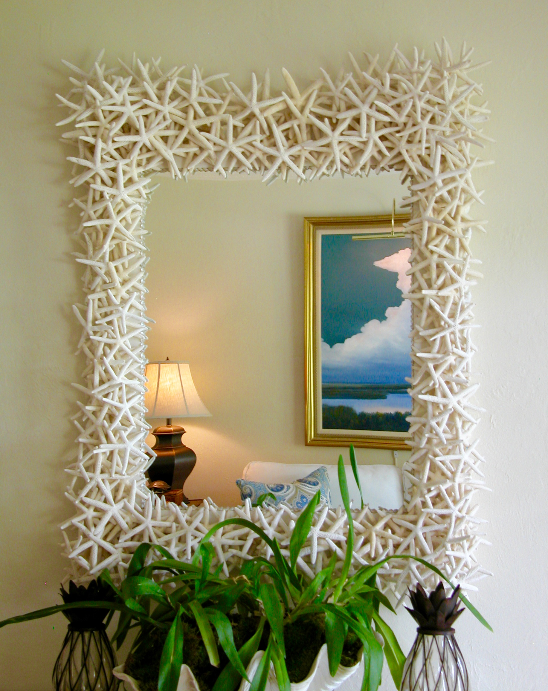 A mirror made with lots and lots of white starfish hangs on a wall with plant on a table under it.