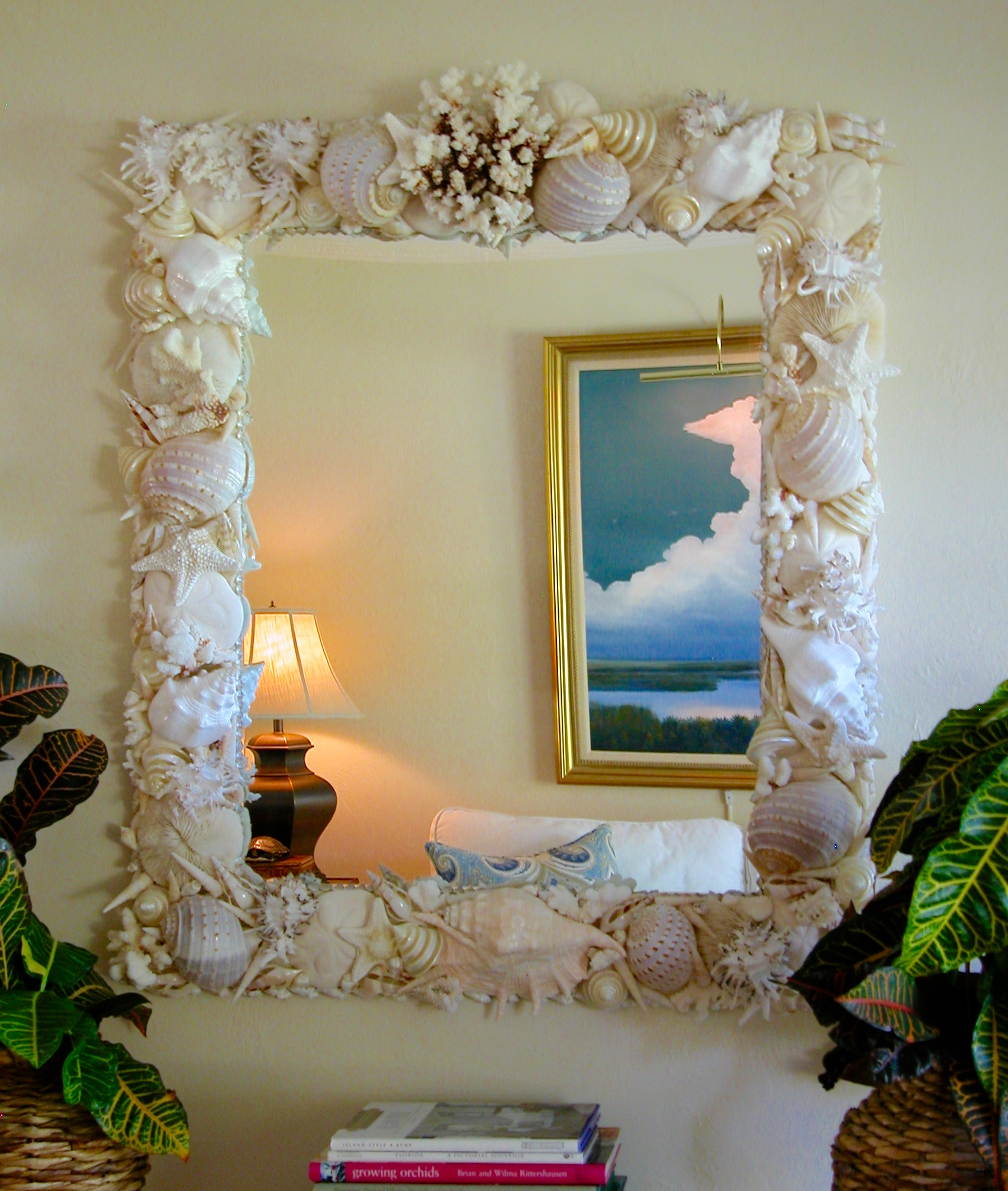 Shell mirror made with large chunky white shells hangs on a white wall.