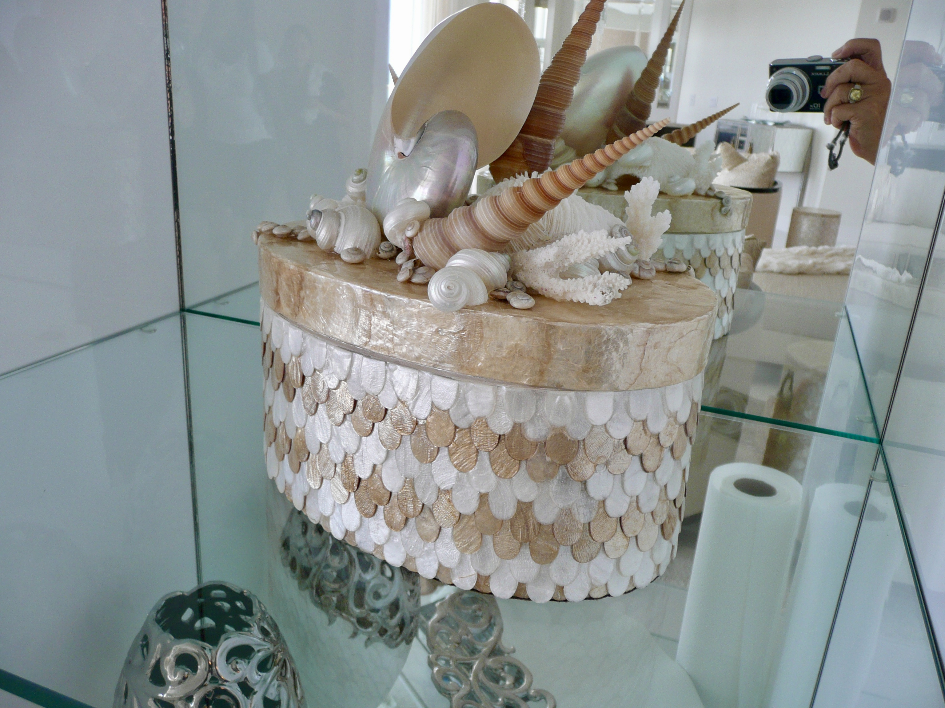 An oval box made with white and tan mother of pearl shells sits on a glass table.