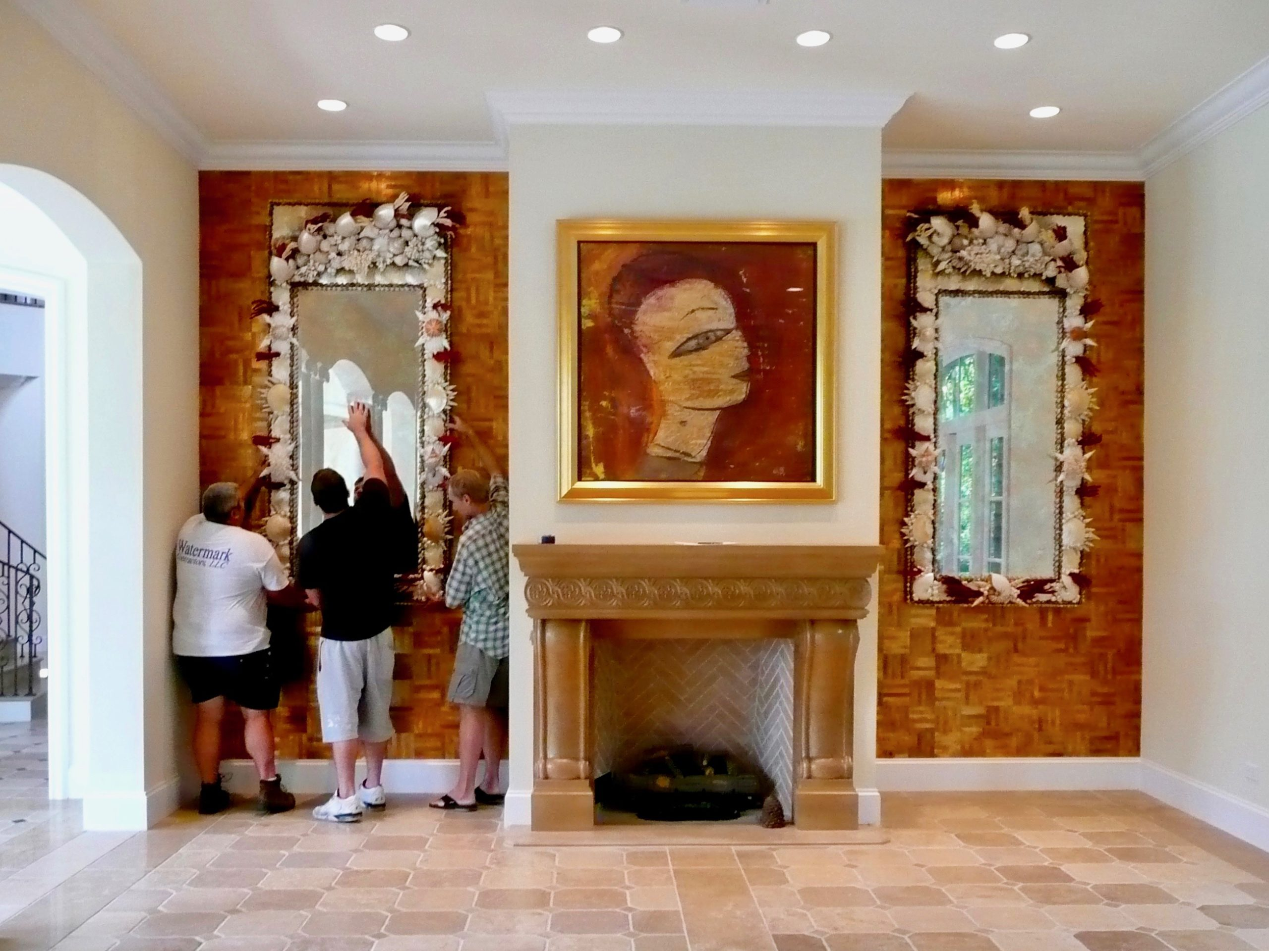 A room with a fireplace with a large painting of a face and three men hanging a huge shell mirror on the wall next to it.