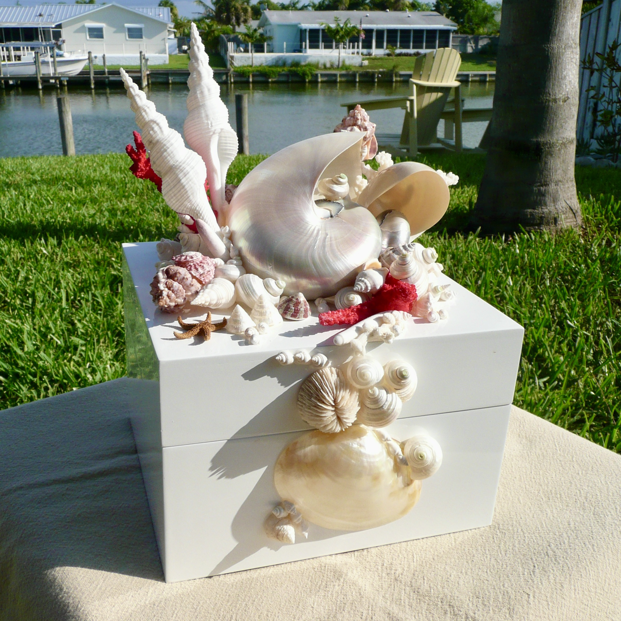 A white lacquered box with white and red shells placed on the sides and top.