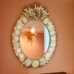 oval mirror made with seashells and coral at the top. hung on a coral colored wall. reflecting a chandelier