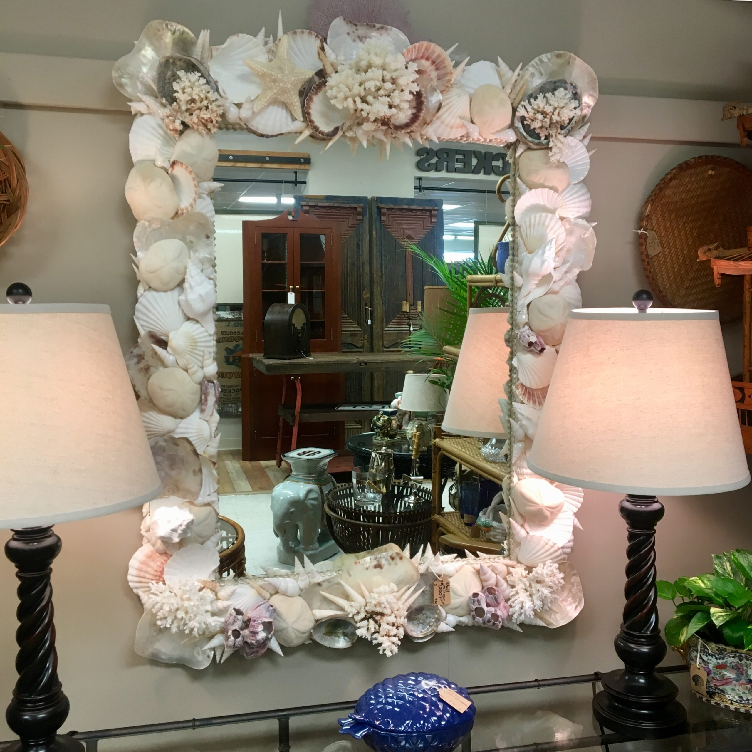 Shell mirror made with large white shell and large pieces of white coral at the top and bottoms hung on a beige wall . A pair of brown lamps with white shades sit on on table underneath.