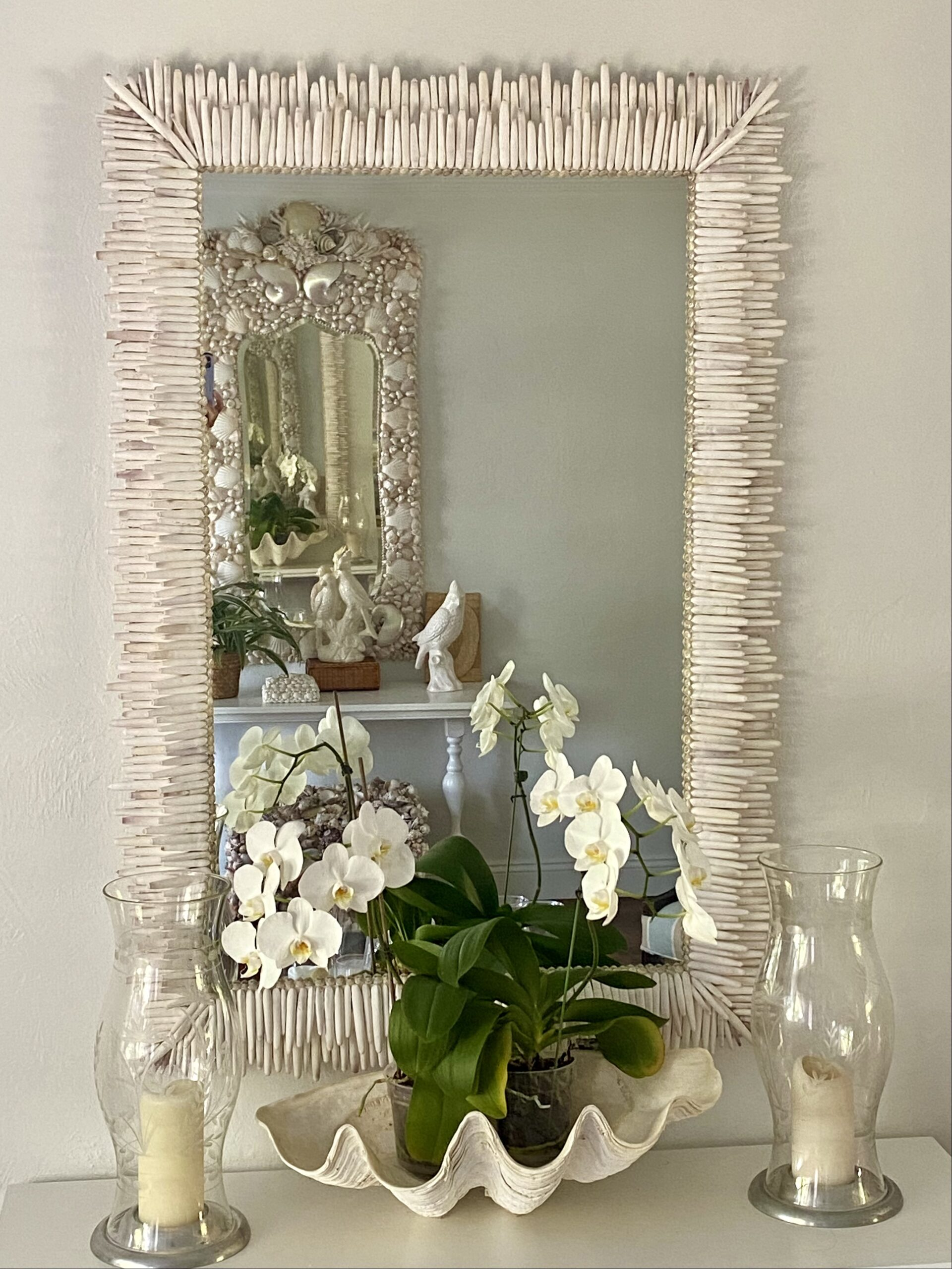 Two white mirrors made with sea shell reflecting each other . White orchids and candles between them.