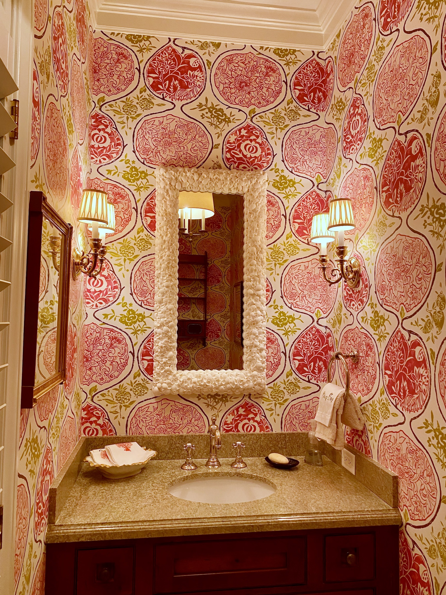 rectangular mirror made with white shells hung on pink floral wallpaper in a bathroom