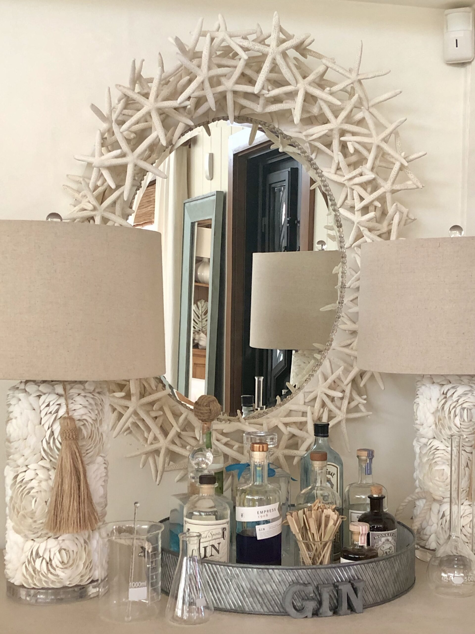 Pair of white lamps in front of a mirror made with starfish.