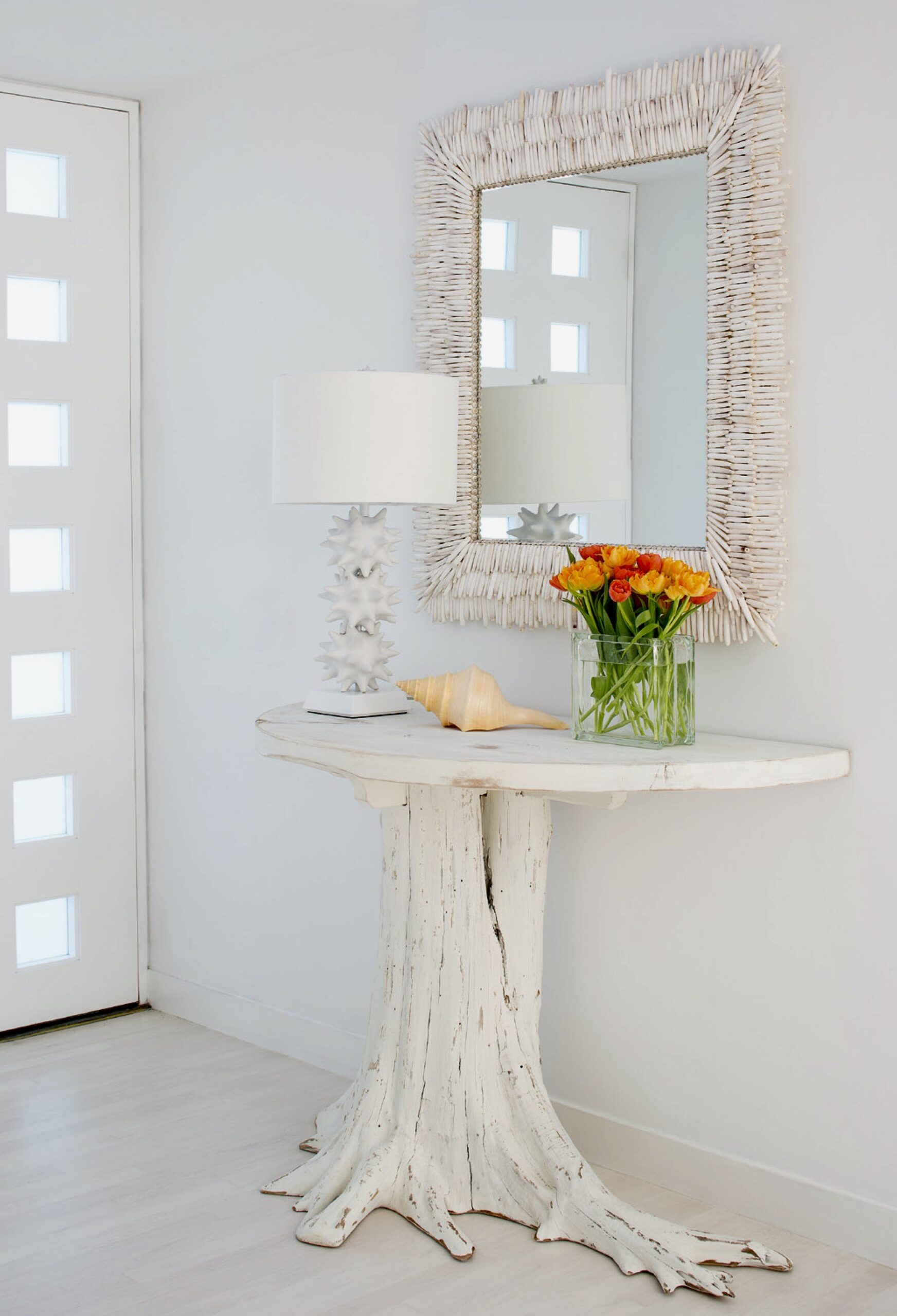 A white shell mirror made with albino urchin spines hung in a foyer over a table made from a try stump