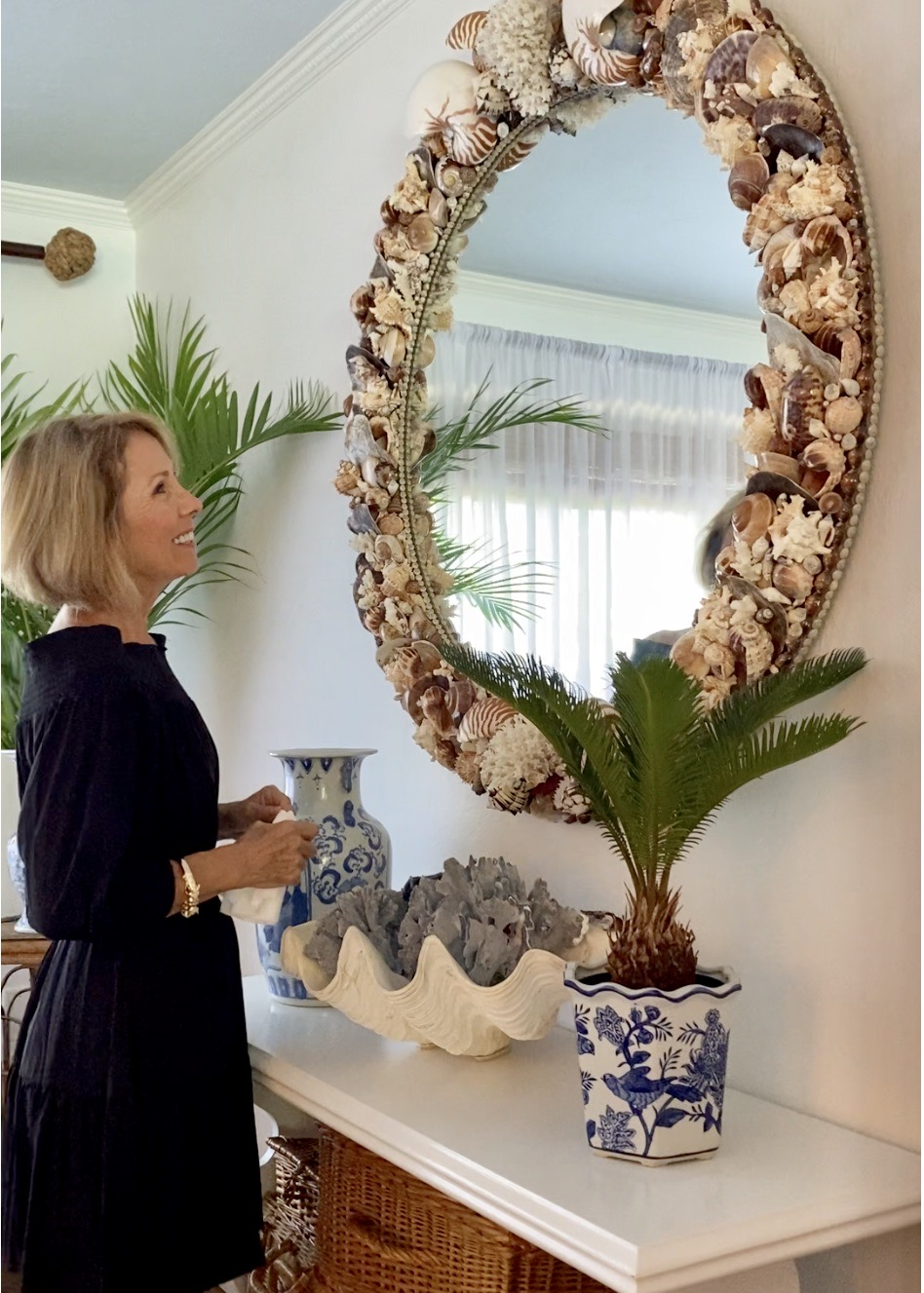 woman standing in front of a large brown mirror made with shells